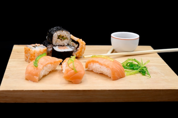 Sushi on wooden table on black isolated background.