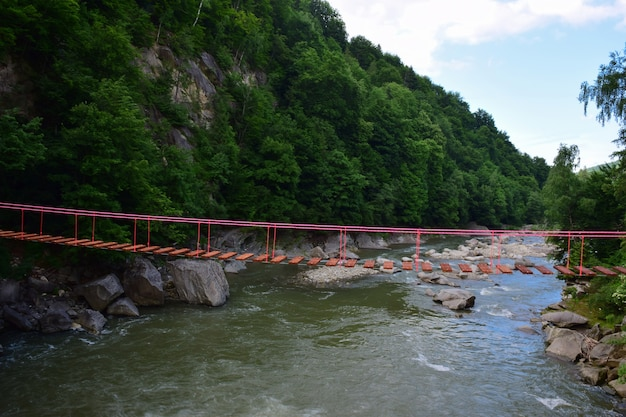Suspended rope bridge without people between rocky banks over a mountain river against the backdrop of a mountain in lush green vegetation