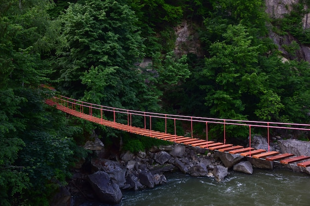 Suspended rope bridge without people with rocky banks over a mountain river against a background of a mountain in lush green vegetation