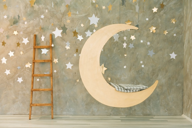 Suspended swing in the shape of the moon with stars.