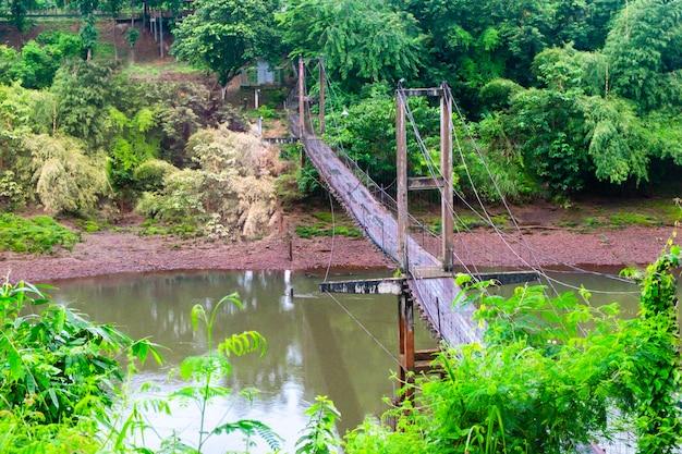 熱帯林に囲まれたジャングル湖を渡る吊り下げられた木製の橋