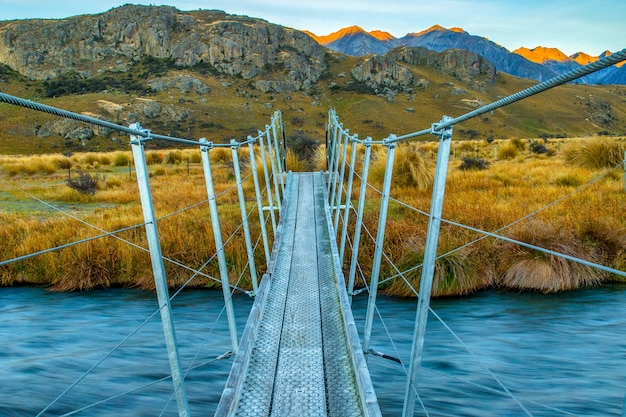 Подвесной мост через ручей, ведущий к горам южных альп