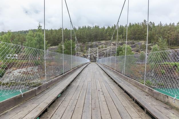 Висячий мост через горную реку с чистой бирюзовой водой. поход в норвегию. горная река с пешеходным мостом. суровая природа норвегии