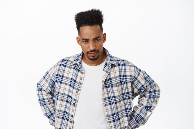 Подозрительный афро-американский парень, недоверчиво щурясь, держась за талию и морщив брови, озабоченный, серьезный на белом