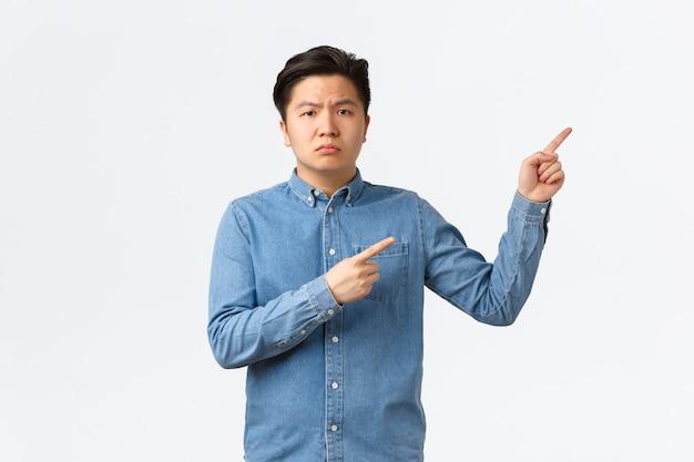 青いシャツを着た不審で疑わしいアジア人男性、懐疑的で不機嫌な眉をひそめ、右上隅に指を指して、質問をし、何か気になること、白い背景に不平を言っています。