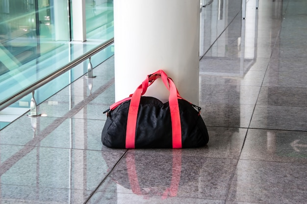 Suspicious black and red bag left unattended in an empty hall. concept of terrorism and public safety. dangerous ownerless derelict luggage.