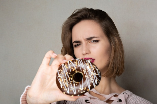 灰色の背景にドーナツを保持しているナチュラルメイクの不審なブルネットの少女。テキスト用のスペース