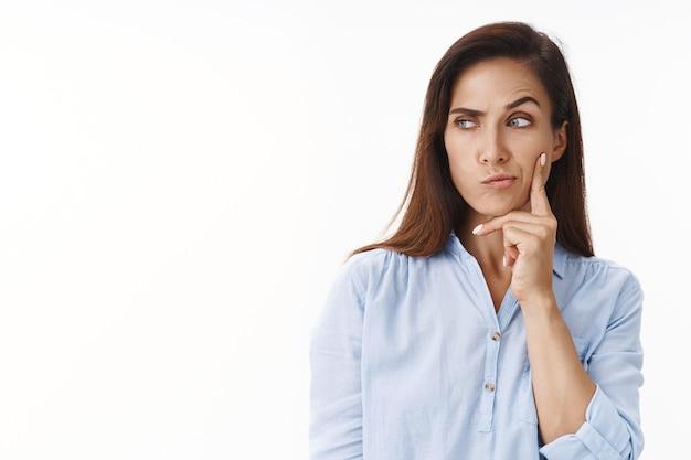 不審なブルネットの中年妻はいくつかの考えを持っています、ずる賢い、目を細めて思慮深く、奇妙な状況を熟考し、左に横向きのコピースペースを見て、頬に触れ、白い壁を考えます