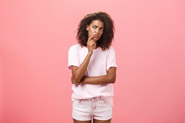 Подозрительная темнокожая молодая кудрявая женщина в футболке трогает подбородок и с сомнением смотрит влево