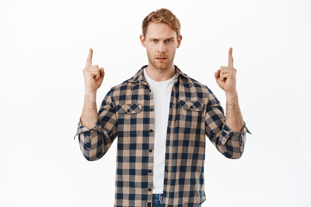 Suspicious displeased redhead man, having doubts, pointing fingers up and looking skeptical or doubtful, express disbelief, standing over white wall