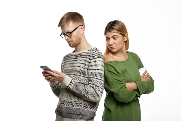 Suspicious distrustful young blonde female in green top standing next to her bearded boyfriend, looking over his shoulder, spying over him while he is typing message using mobile phone