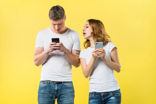 노란색 배경으로 휴대 전화에 그의 남자 친구 문자 메시지를 감시 의심스러운 여자 친구