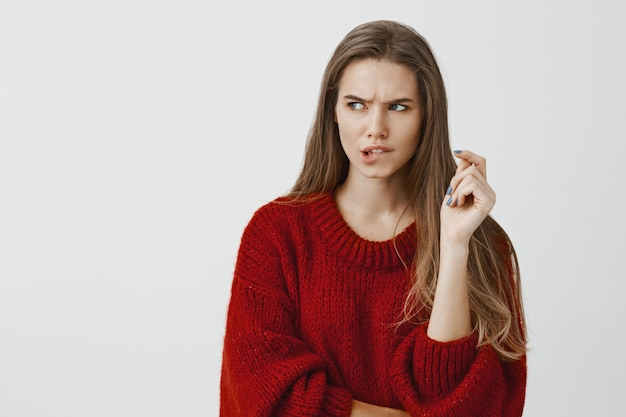 Suspicious girlfriend trying to think up way to pick password of smartphone. portrait of focused anxious good-looking female, biting lip and frowning, looking aside, thinking solution to issue