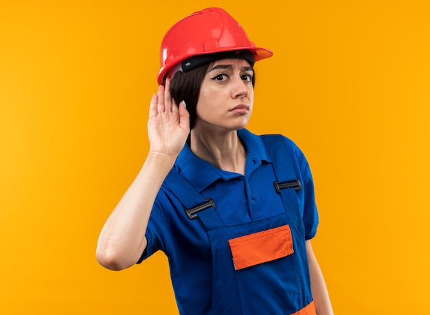 Suspicious looking at camera young builder woman in uniform showing listen gesture
