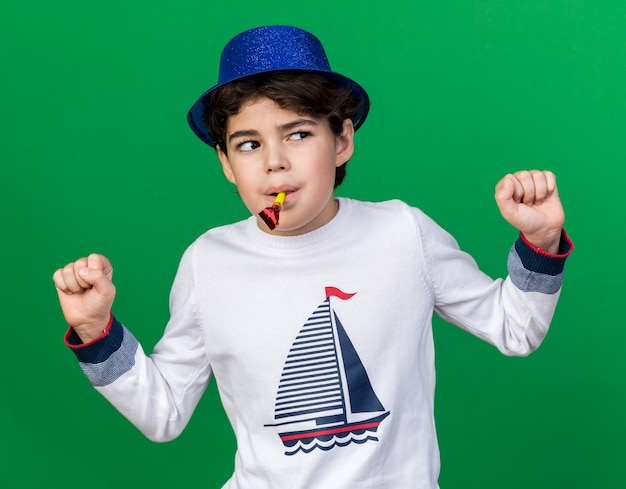 Suspicious looking side little boy wearing blue party hat blowing party whistle showing yes gesture isolated on green wall