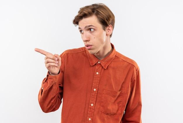 Il giovane bel ragazzo dal lato dall'aspetto sospettoso che indossa una maglietta rossa indica il lato isolato sul muro bianco