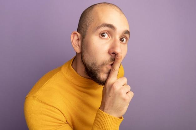 Подозрительно смотрящий прямо перед собой молодой красивый парень, показывающий жест тишины на фиолетовом фоне с копией пространства