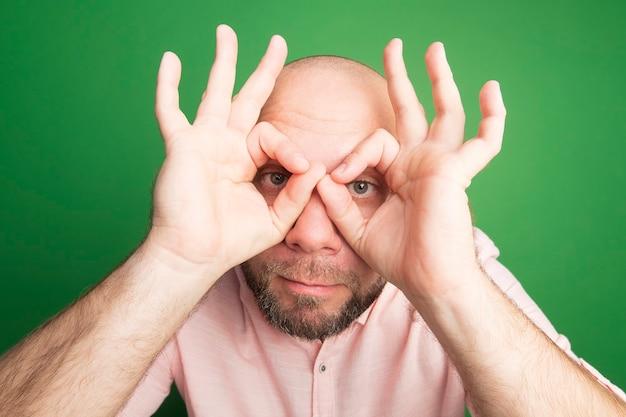 Uomo calvo di mezza età sospettoso che indossa la maglietta rosa che mostra il gesto di sguardo isolato sul verde