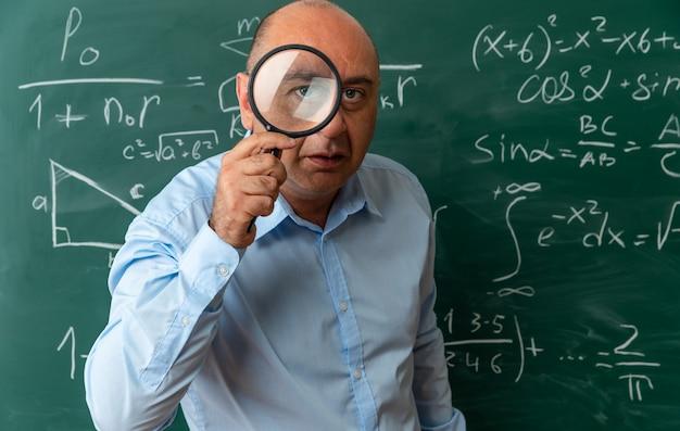 Insegnante maschio di mezza età sospettoso in piedi davanti alla lavagna guardando la telecamera con la lente d'ingrandimento