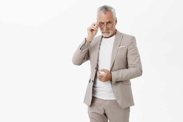 Подозрительный серьезный старик в костюме скептически смотрит поверх очков