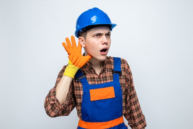 Suspicious showing listen gesture young male builder wearing uniform with gloves