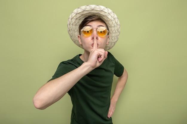不審な表示沈黙ジェスチャー眼鏡をかけた帽子をかぶった若いハンサムな男
