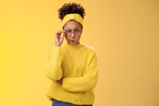 의심스러운 엄격한 진지한 외모의 매력적인 영리한 아프리카계 미국인 여학생 체크 안경을 비웃는 듯한 인상을 찡그리며 불쾌한 반 친구의 행동이 의심스러운 표정을 짓고 있습니다.