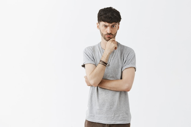 Suspicious and thoughtful handsome guy posing against the white wall
