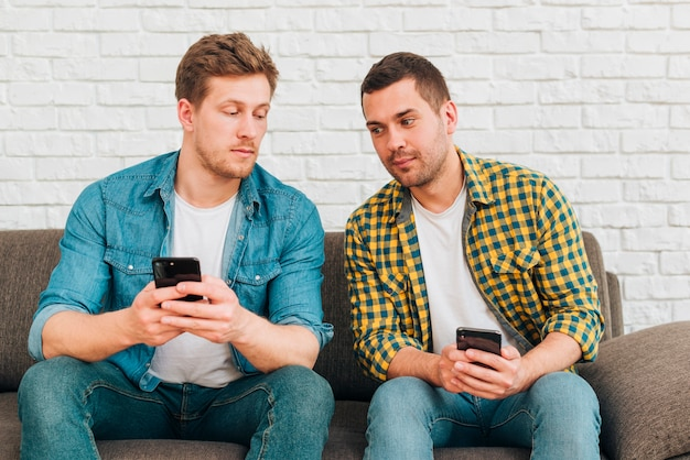 Suspicious two male friends sitting on sofa using mobile phone