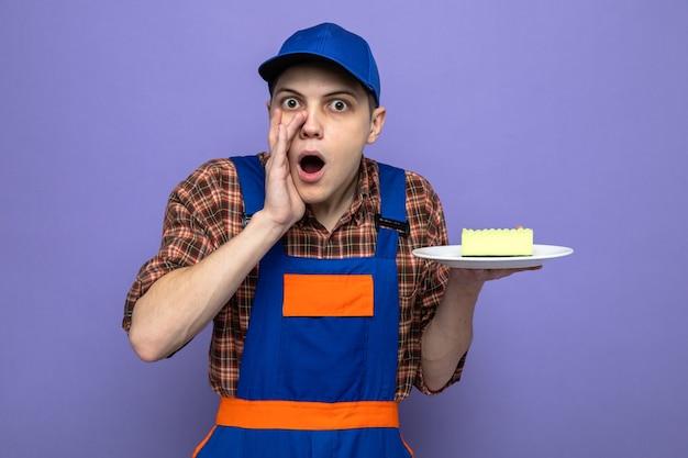 不審なささやき制服と皿にスポンジを保持しているキャップを身に着けている若い掃除人