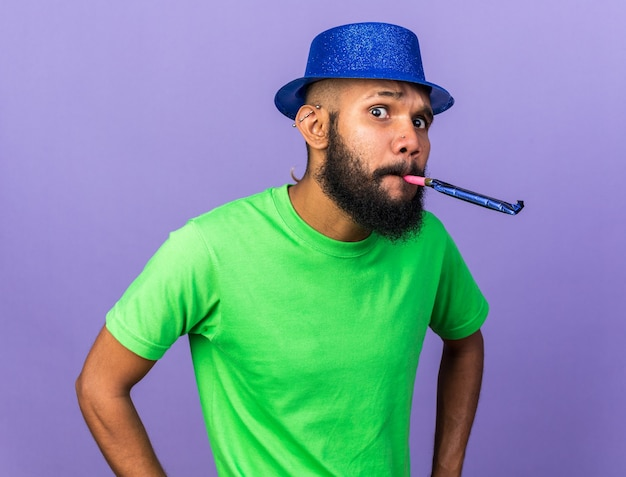 Suspicious young afro-american guy wearing party hat blowing party whistle