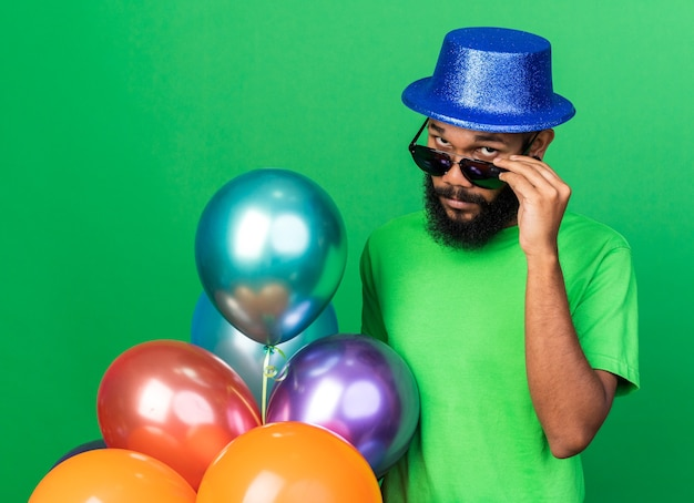 Suspicious young afro-american guy wearing party hat and glasses holding balloons