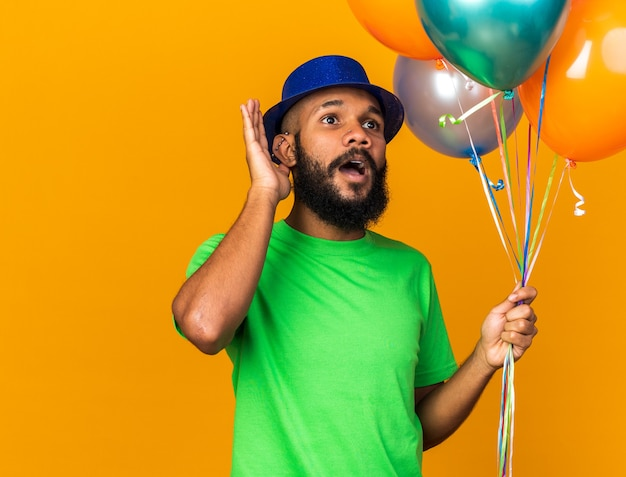 Suspicious young afro-american guy wearing party hat holding balloons showing listen gesture