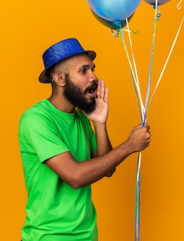 Suspicious young afro-american guy wearing party hat holding balloons whispers isolated on orange wall