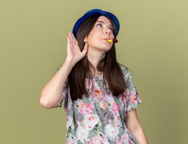 Suspicious young beautiful girl wearing party hat blowing party whistle showing listen gesture