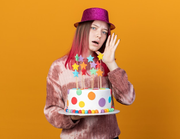 La giovane bella ragazza sospettosa che indossa il cappello del partito che tiene la torta sussurra isolata sulla parete arancione