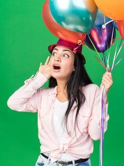 緑の壁に分離されたリスニングジェスチャーを示す風船を保持しているパーティーハットを身に着けている不審な若い美しい女性