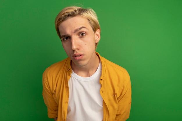 Подозрительный молодой блондин в желтой футболке на зеленом фоне с копией пространства