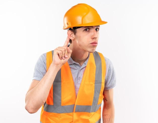 Il giovane uomo sospettoso del costruttore in uniforme che mostra ascolta il gesto isolato sul muro bianco