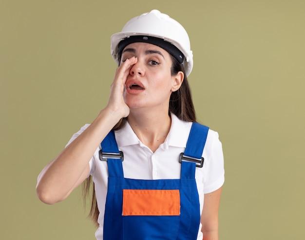 Подозрительная молодая женщина-строитель в униформе шепчет на оливково-зеленой стене