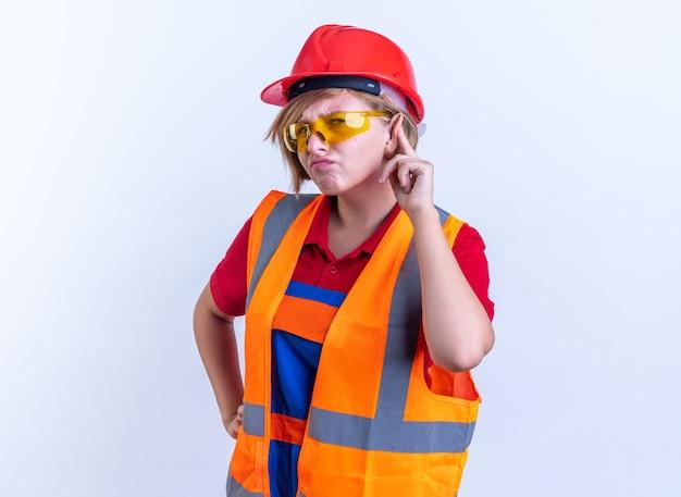 白い背景で隔離のリッスンジェスチャーを示す眼鏡と制服を着た不審な若いビルダーの女性