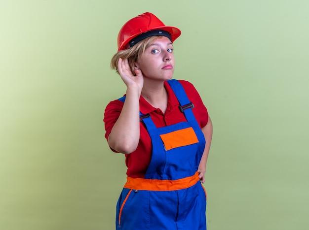 Sospettosa giovane donna costruttore in uniforme che mostra gesto di ascolto isolato su parete verde oliva