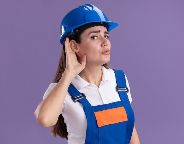 Donna sospettosa giovane costruttore in uniforme che mostra ascolta gesto isolato sulla parete viola