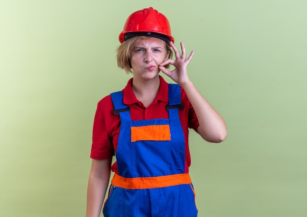 Sospettosa giovane donna costruttore in uniforme che mostra gesto di silenzio isolato su parete verde oliva