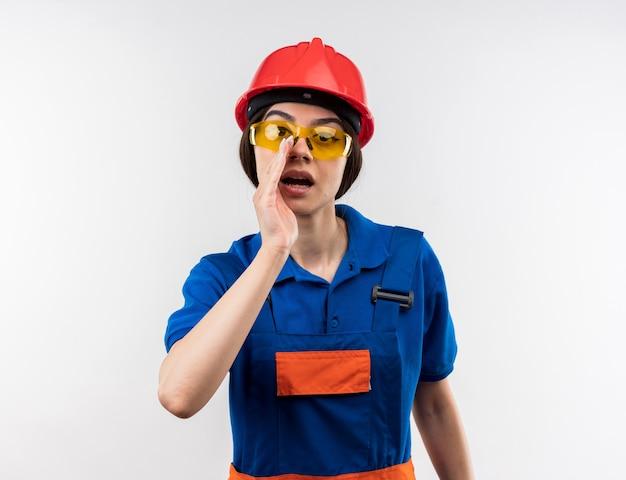Sospettosa giovane donna costruttore in uniforme con gli occhiali che chiama qualcuno