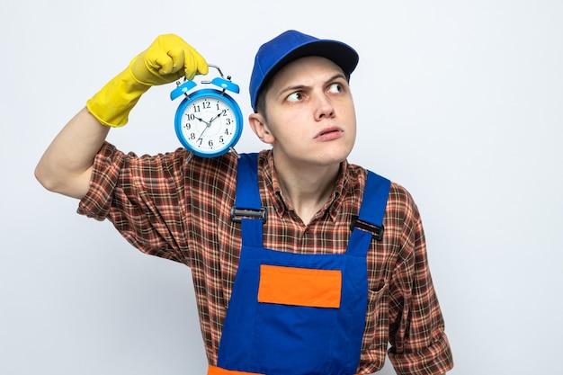 Giovane ragazzo delle pulizie sospettoso che indossa l'uniforme e il berretto con i guanti che tengono la sveglia
