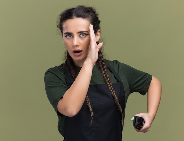 Sospettoso giovane donna barbiere in uniforme che tiene i sussurri di tagliacapelli isolati sulla parete verde oliva