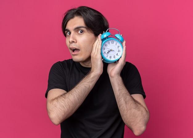 Подозрительный молодой красивый парень в черной футболке держит будильник вокруг уха, изолированного на розовой стене