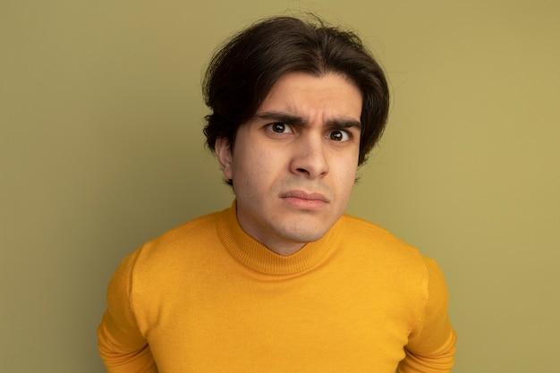 Sospettoso giovane bel ragazzo che indossa un maglione dolcevita giallo isolato sulla parete verde oliva