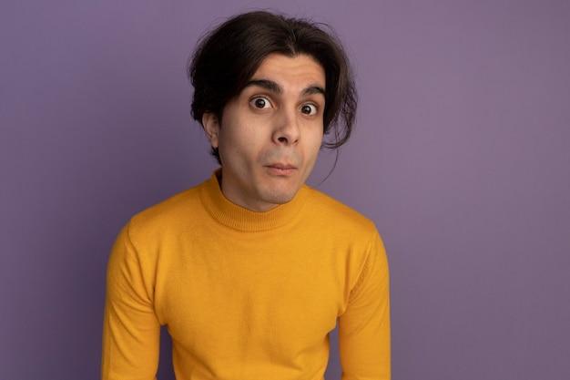 Sospettoso giovane bel ragazzo che indossa un maglione dolcevita giallo isolato sulla parete viola con lo spazio della copia